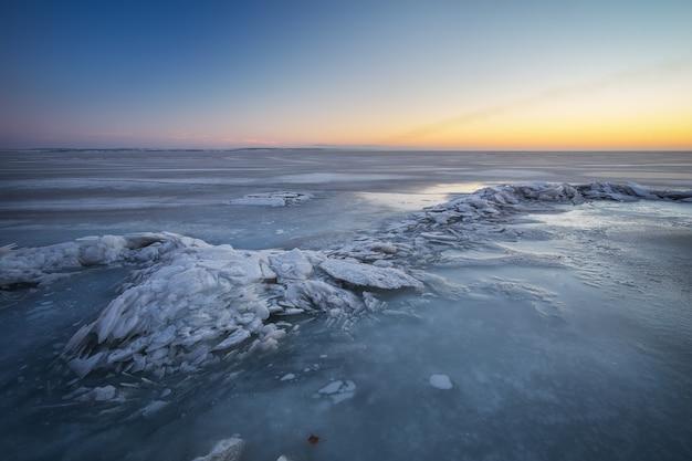 Paesaggio invernale con lago ghiacciato e cielo infuocato al tramonto. composizione della natura.