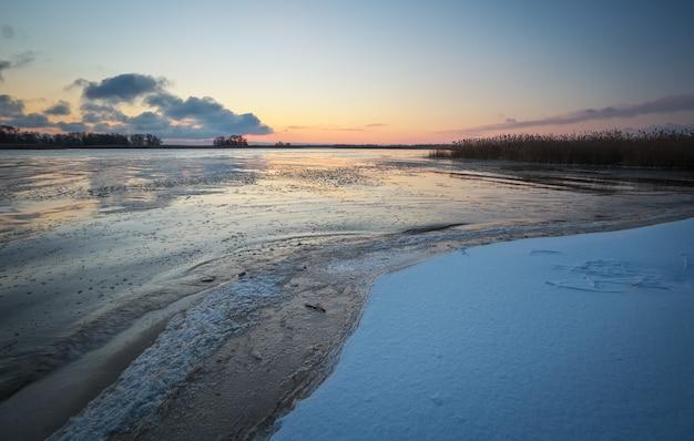 Paesaggio invernale con lago ghiacciato e cielo al tramonto. cielo arancione colorato. composizione della natura.