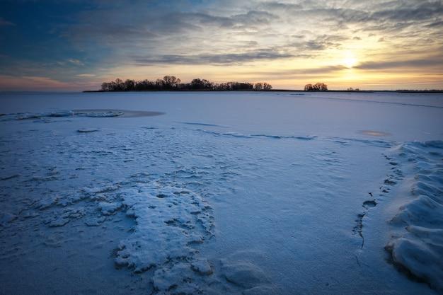 Paesaggio invernale con lago ghiacciato e cielo al tramonto. composizione della natura.