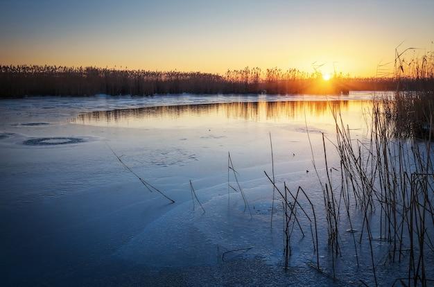 Paesaggio invernale con fiume ghiacciato, canneti e cielo al tramonto. alba