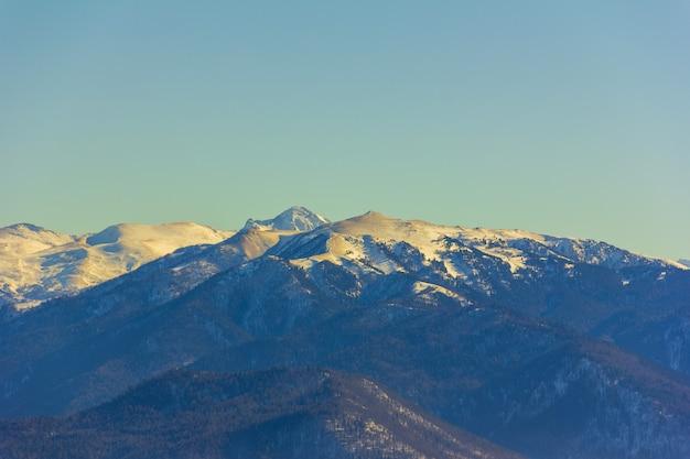 Paesaggio invernale con montagne e colline ricoperte di neve e sabbia dopo la tempesta di sabbia africana