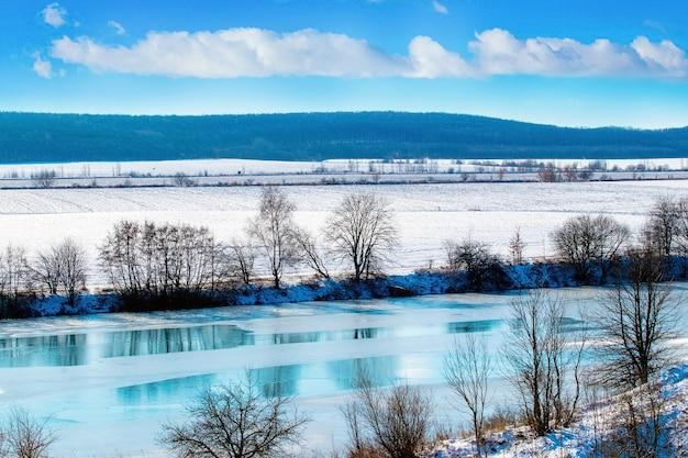 Paesaggio invernale con fiume e campo nevoso in una giornata di sole