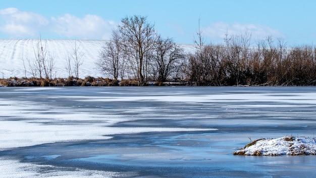 Paesaggio invernale con un fiume che gela