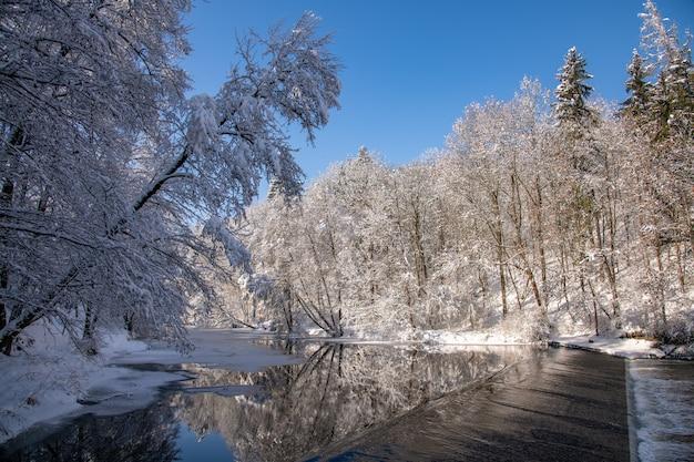 Paesaggio invernale con fiume e sbarramento