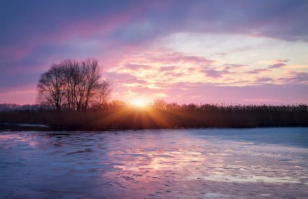 Paesaggio invernale con sole all'alba e fiume ghiacciato.