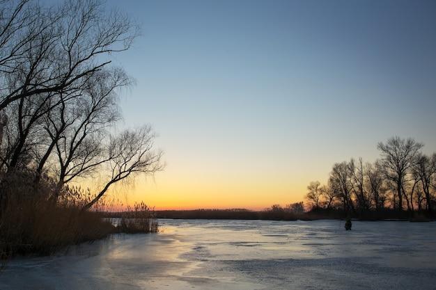 Paesaggio invernale con cielo al tramonto e fiume ghiacciato. pescatore sul lago d'inverno