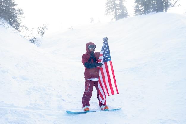 Inverno, tempo libero, sport e concetto di persone: lo snowboarder siede in alto sulle montagne sul bordo del pendio e guarda in lontananza. snowboarder che tiene bandiera americana