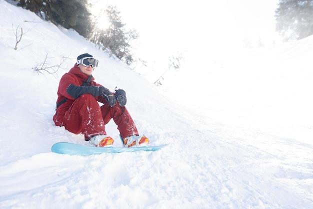 Inverno, tempo libero, sport e concetto di persone: lo snowboarder siede in alto sulle montagne sul bordo del pendio e guarda in lontananza.