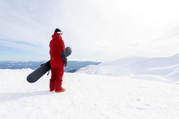 Inverno, tempo libero, sport e concetto di persone: lo snowboarder si trova su un pendio di backcountry e tiene lo snowboard. concetto di sci