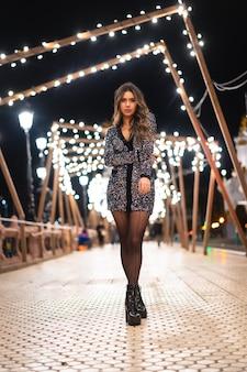Stile di vita invernale a natale. bruna ragazza caucasica in un vestito alla moda con paillettes e tacchi alti neri, su un ponte sul fiume della città con luci di natale