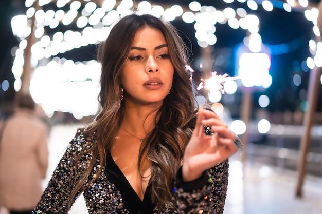 Stile di vita invernale a natale. bruna ragazza caucasica in un vestito alla moda con paillettes, sorridente su un ponte sul fiume della città con luci di natale con una torcia fiammeggiante e scintille