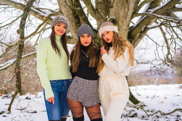Stile di vita invernale, tre bellissimi amici caucasici che si godono la neve in inverno sotto un albero, vacanze nella natura
