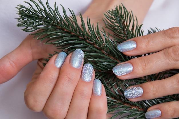 Manicure invernale sulle mani della donna con ramo di abete