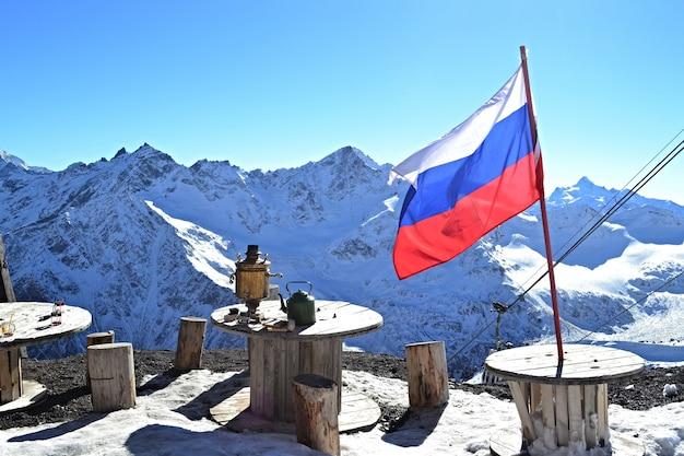 Paesaggio montano invernale, bandiera russa, samovar e caffè in montagna