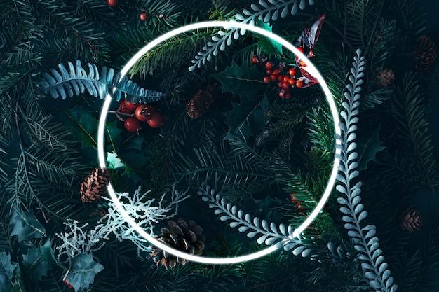 La natura invernale è piatta realizzata con rami di abete, pigne e foglie innevate. natale creativo con cornice rotonda.