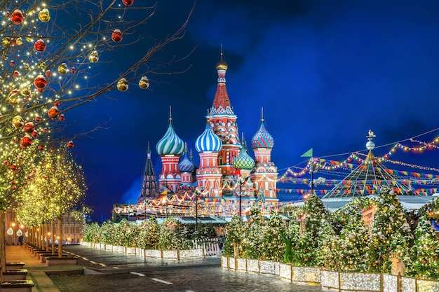 Notte d'inverno sulla piazza rossa di mosca e cattedrale di san basilio e addobbi natalizi su abeti e alberi