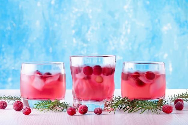 Cocktail analcolico invernale con mirtillo rosso e ghiaccio su sfondo blu brillante, primo piano