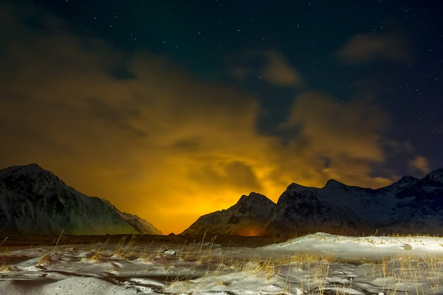 Inverno norvegia. erba ricoperta di neve nella valle notturna. le luci della città mettono in risalto le nuvole dietro le montagne