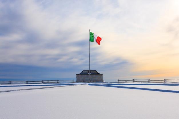 Panorama invernale dalle alpi italiane. primo monumento ai caduti della guerra mondiale. bandiera italiana sventolante