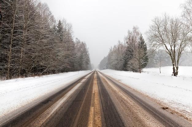 Strada asfaltata invernale con solchi di automobili in inverno