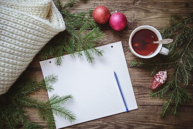 Blocco note con foto invernali con penna, tazza di tè, rami di abete