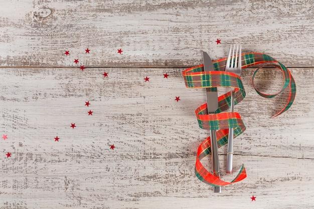 Regolazione di posto invernale con decorazioni di natale e capodanno sulla tavola di legno bianca. regolazione festiva della tavola per la cena di natale. lay piatto con copia spazio per il testo