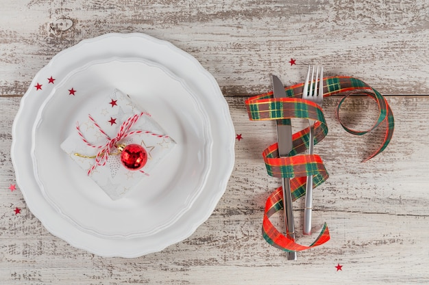 Regolazione di posto invernale con decorazioni di natale e capodanno sulla tavola di legno bianca. regolazione festiva della tavola per la cena di natale. lay piatto