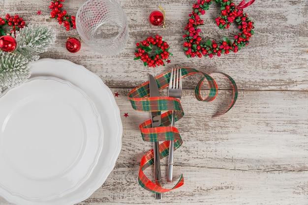 Regolazione di posto invernale con decorazioni di natale e capodanno sulla tavola di legno bianca. regolazione festiva della tavola per la cena di natale. vista dall'alto con copia spazio per il testo
