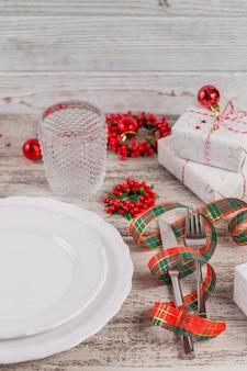 Regolazione di posto invernale con decorazioni di natale e capodanno sulla tavola di legno bianca. regolazione festiva della tavola per la cena di natale.