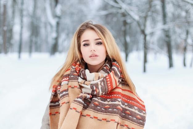 Ritratto di inverno di una bella ragazza in abiti alla moda in piedi in una giornata invernale all'aperto Foto Premium