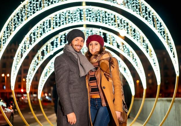 Ritratto di inverno di una coppia caucasica accanto alle luci di natale della città Foto Premium
