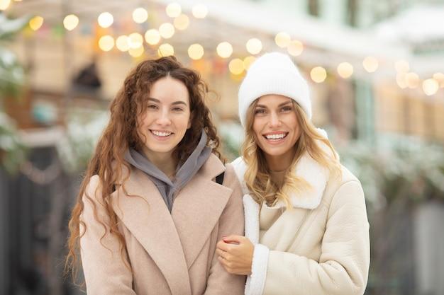 Ritratto di inverno di moda sorridente amici femminili. donna felice che ha divertimento all'aperto.