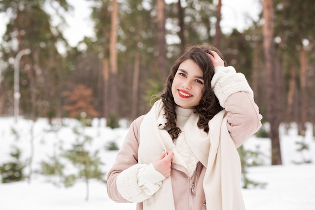 Il ritratto invernale di una donna bruna felice indossa una sciarpa e un cappotto caldo che cammina nella foresta. spazio vuoto