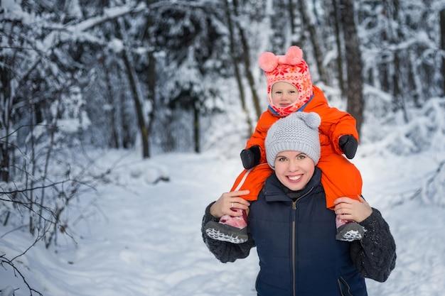 Ritratto di inverno di mamma e bambino nella foresta di neve.