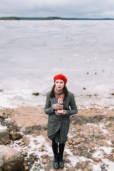 Inverno ritratto di giovane donna in un cappotto e cappello rosso che tiene faro decorativo e in piedi sulla riva del mare ghiacciato. inverno, viaggi, sfondo del mare. tempo ventoso, incredibile mare ghiacciato