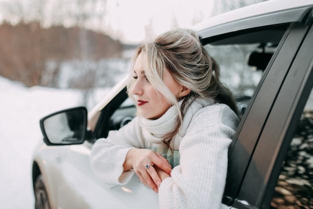 Concetto di viaggio su strada invernale, ragazza in viaggio felice guardando fuori dal finestrino in natura