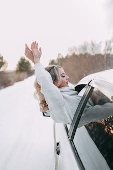 Concetto di viaggio su strada invernale, ragazza in viaggio felice guardando fuori dal finestrino della macchina