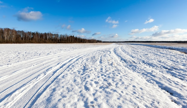 Strada invernale con solchi dalle auto in inverno, ricoperta di neve dopo la nevicata, solchi dalle auto sulla strada nel campo