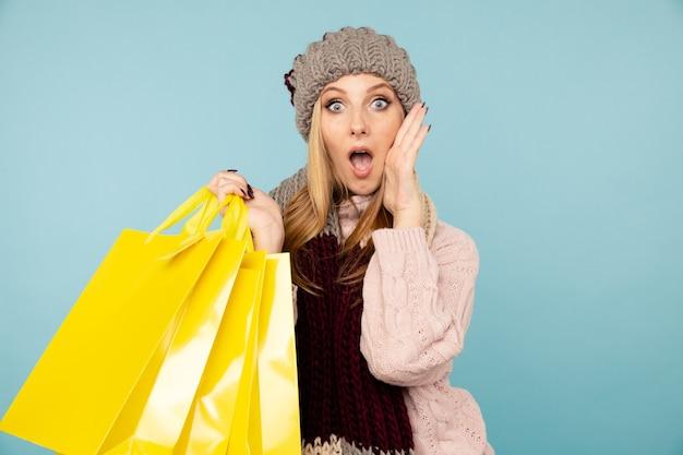 Concetto di vendita invernale. donna sorpresa nel cappello con i sacchetti della spesa gialli.