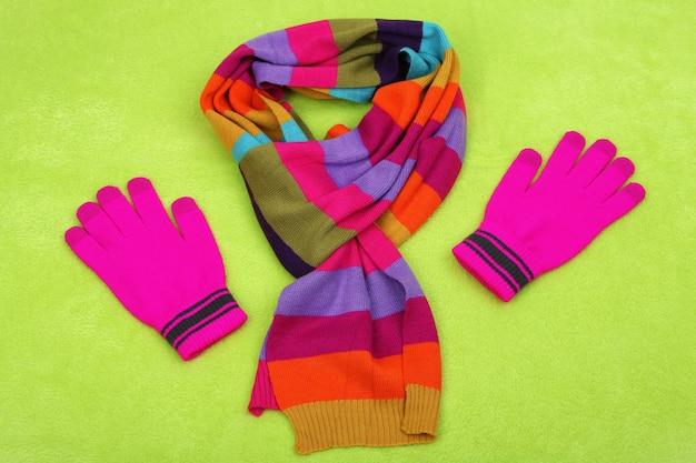 Sciarpa e guanti invernali, su superficie colorata
