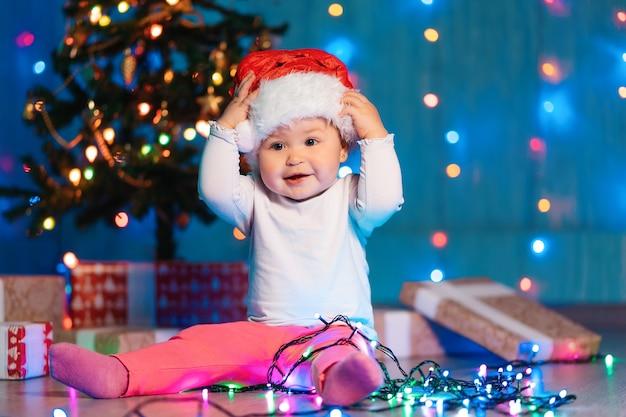 Vacanze stagionali invernali. un bambino divertente tiene in testa un cappello di natale seduto con luci festive e regali di natale. il concetto di natale e capodanno.