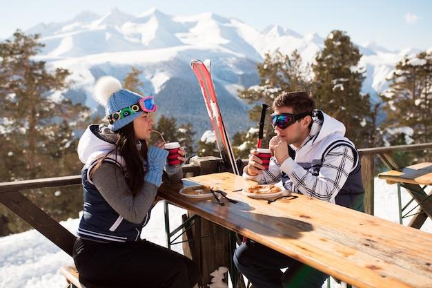 Inverno, sciatori che si godono il pranzo in montagna invernale.