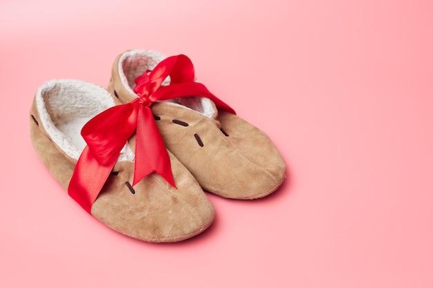 Pantofole invernali con pelliccia in un nastro rosso, su sfondo blu, banner, copia spazio, mock up