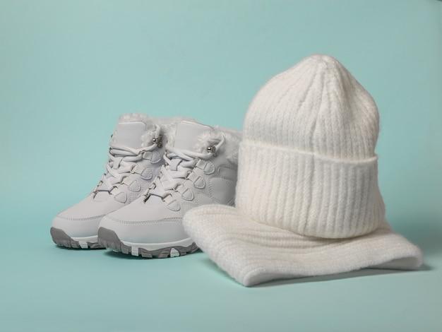 Sneakers invernali con pelliccia, cappello e sciarpa su una superficie blu