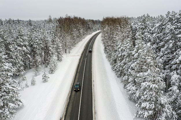 Foresta di conifere coperta di neve invernale e la strada da una vista a volo d'uccello