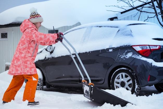 Inverno e nevicate. bambina pulisce la neve con una pala
