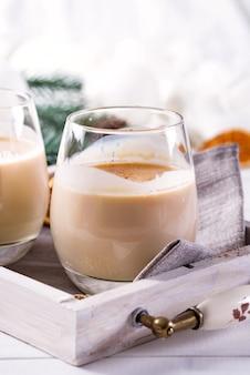 Zabaione bevanda calda piccante inverno in bicchieri con cannella nel vassoio, rami di abete bianco sulla tavola di legno