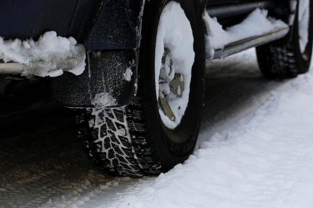 Pneumatici invernali su ruote auto in inverno. nevicata fuori città