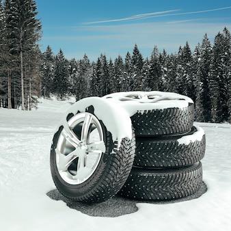 Pneumatici invernali con cerchi sportivi. sfondo con alberi e neve. rendering 3d