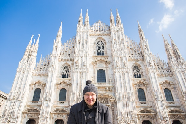 Concetto di viaggio, vacanze e persone di inverno - turista maschio bello che fa la foto del selfie davanti al duomo famoso a milano.